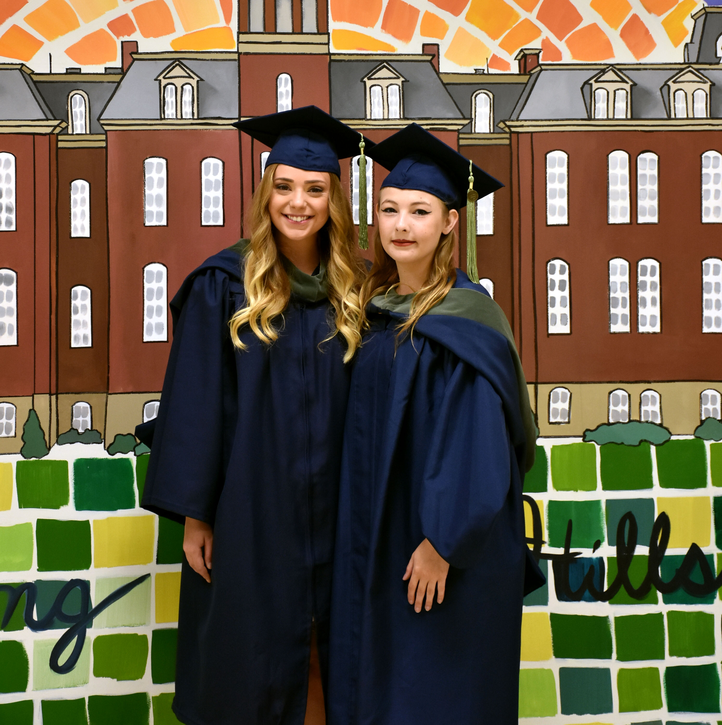 Jessica Armes and Catherine Waldron wait to walk in the commencement ceremony